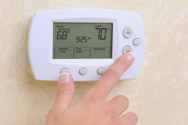 closeup of hand setting a thermostat - What We Inspect